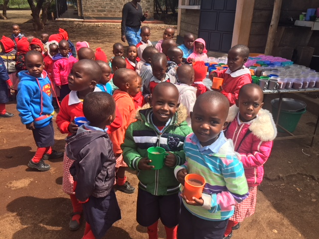 Children enjoying their mid-morning break. They are well wrapped up, as not everywhere in Africa is warm!